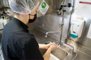 Employée de restauration collective se désinfectant les mains