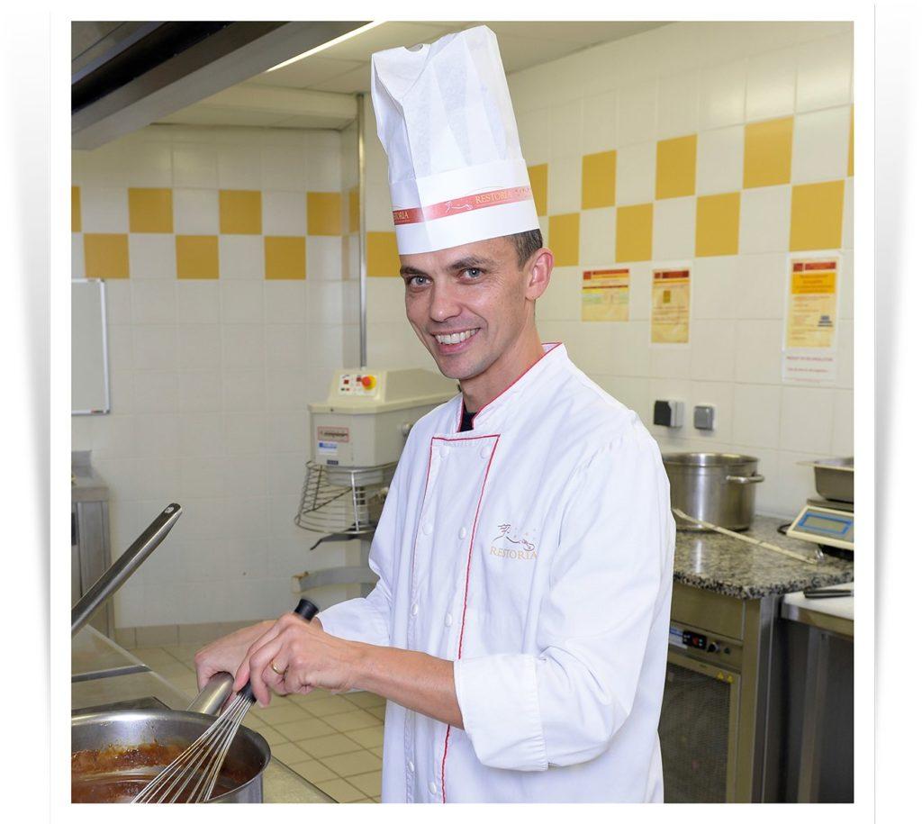 Chef gérant souriant en cuisine en restauration collective.