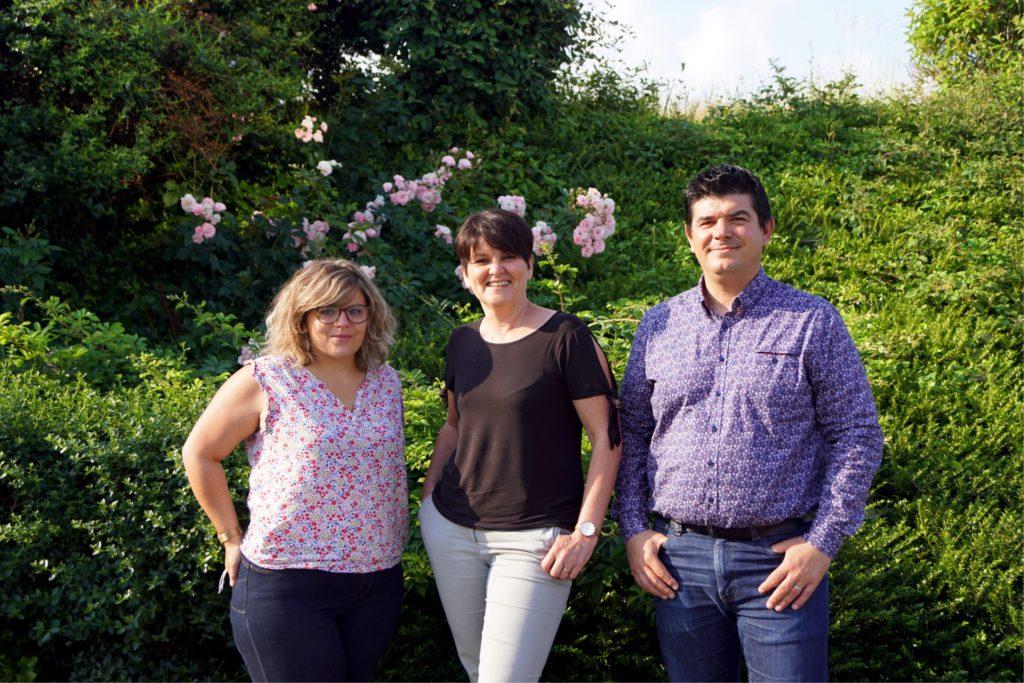 Trois membres de l'équipe du Savoir Partagé devant un buisson.