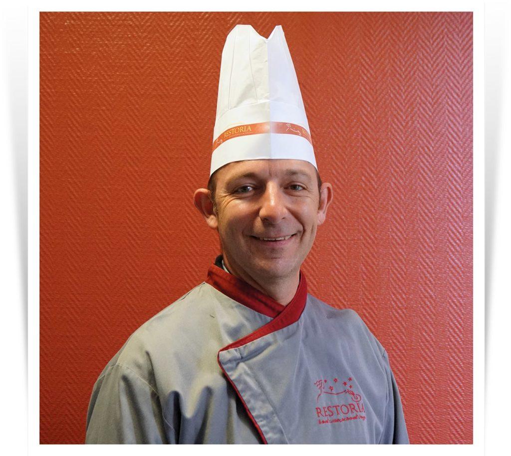 Portrait d'un formateur métier en restauration collective en tenue de cuisine.