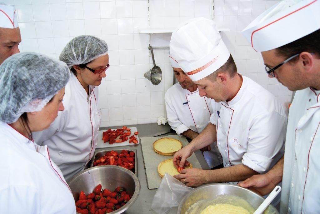 employés de restauration collective réalisant des pâtisseries élaborées