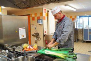 Cuisinier coupant des légumes d'accompagnement