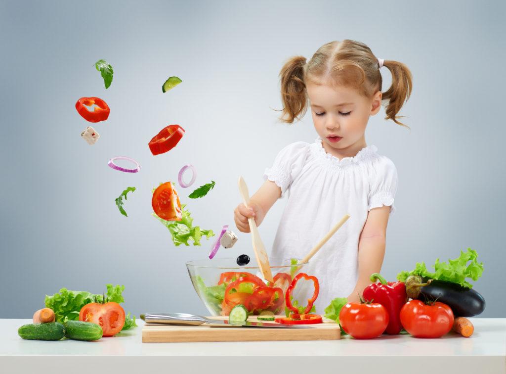 Petite fille coupant des légumes